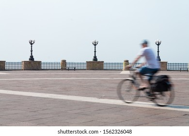 "Taranto, Italy - August 15, 2015: Cyclist walks through the square ""La Rotonda"", bicycle with bag, in the background the streetlights, was used the photographic technique of the long exhibition."