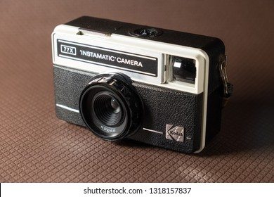 Taranto, Italy - February 19, 2019: Vintage film camera, Kodak brand, Instamatic camera 77x model, photographed on a brown background with squared texture.