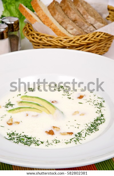 """""""Tarator"""" cold soup with avocado and tarragon on a white plate with fennel"""