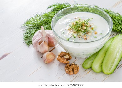 Tarator soup ingredients - yogurt, cucumber, dill, walnuts, garlic, oil, white wood background