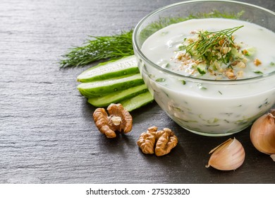 Tarator soup and ingredients - yogurt, cucumber, dill, walnuts, garlic, oil, dark stone background, closeup