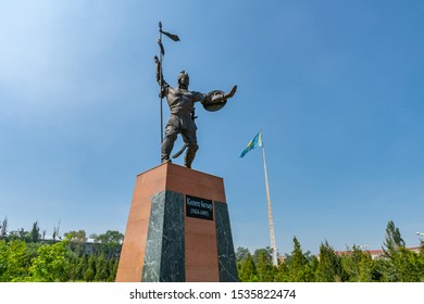 TARAZ, KAZAKHSTAN - MAY 2019: Presidential Park Statue of Koshek Batyr Holding a Spear with Huge Waving Kazakhstan Flag at Background on a Sunny Blue Sky Day