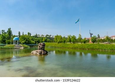 TARAZ, KAZAKHSTAN - MAY 2019: Presidential Park View of Lake Pavilion and Statue of Koshek Batyr Holding a Spear on a Sunny Blue Sky Day
