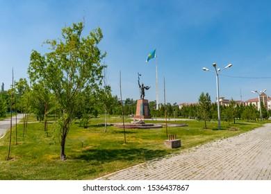 TARAZ, KAZAKHSTN - MAY 2019: Presidential Park Statue of Koshek Batyr Holding a Spear with Huge Waving Kazakhstan Flag at Background on a Sunny Blue Sky Day