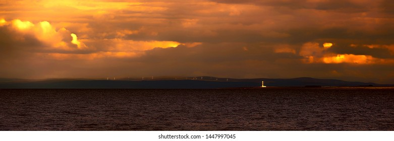 Tarbat Ness lighthouse lit up in late evening summer sunset light with Rothes wind farm across the Moray Firth in the distance.