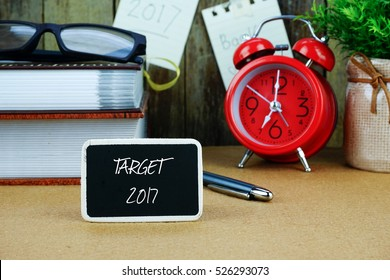TARGET 2017 inscription written on chalkboard. Red alarm clock, books, spectacle, notes at background.