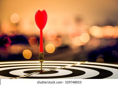 target dart with arrow over blurred bokeh background ,metaphor to target marketing or target arrow concept.