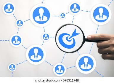 Target Teamwork Business Social Network Communication concept. Hand with magnifying glass shows goal against background of network of people on a virtual graphical user interface.