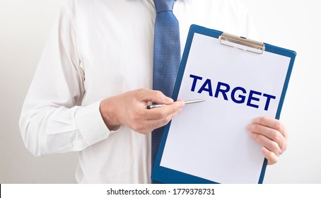 TARGET word written on paper board in hands of businessman in shirt and tie