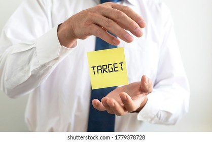 TARGET word written on yellow paper note flying between hands of businessman in shirt and tie. going to target or reaching target concept