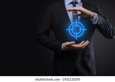 Targeting concept with businessman hand holding target icon dartboard sketch on chalkboard. Objective target and investment goal concept