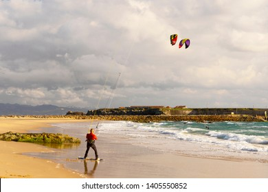 TARIFA, ANDALUSIA, SPAIN - APRIL 4 2019: Young man is getting ready for kitesurfing tricks. Tarifa is a paradise for nature and watersports lovers, Cadiz Province, Andalusia, southern Spain, Europa.