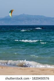 Tarifa. Kiteboarder goes along the Los Lances beach by the Atlantic Ocean.