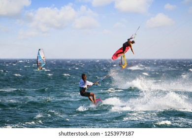 TARIFA, SPAIN – SEPTEMBER 08, 2018. Windsurfer sailing fast and jumping across the Los Lances Beach in the west coast of Tarifa Village, in Cadiz.
