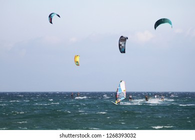 TARIFA, SPAIN – SEPTEMBER 08, 2018. Windsurfers and kitesurfers sailing fast and jumping across the Los Lances Beach in the west coast of Tarifa Village, in Cadiz.