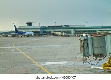 The tarmac at an airport, showing the rear of a passenger plane in the background with an empty gate in the foreground.  Pearson International airport, Toronto, Ontario.