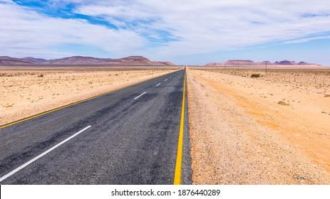 A tarmac highway cuts through the dry, arid landscape of the Namib Desert near Aus, Namibia.