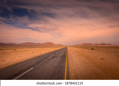 A tarmac highway cuts through the dry, arid landscape of the Namib Desert near Aus at sunset, Namibia.