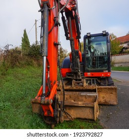 Tarn, France - Dec. 2020 - Front view of an orange, small, compact mini excavator from the Japanese manufacturer of construction equipment Kubota, featuring its hydraulic boom, bucket and front blade