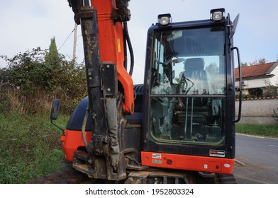Tarn, France - Dec. 2020 - Front view of the windscreen of the operator's cabin an orange, small and compact track-laying mini excavator from the Japanese manufacturer of construction equipment Kubota