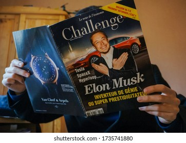 Tarn, France - Feb. 2019 - A man reads an issue of the French economic newspaper Challenges showing the businessman Elon Musk in front of a Tesla, with an advert for a luxury watch brand on the back
