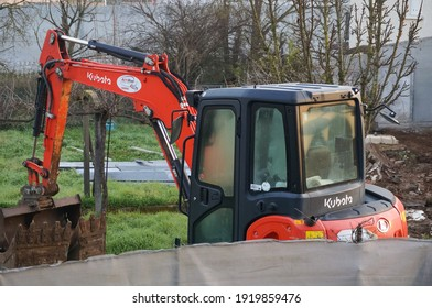 Tarn, France - Feb. 2021 - Operator's cabin, rear and mechanical arm of a red, small, compact mini excavator from the Japanese manufacturer of construction equipment Kubota, used in a garden