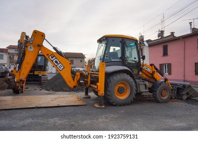 Tarn, France - Feb. 2021 - A yellow tractor from the British manufacturer JCB, parked on a construction site, featuring a front hydraulic loader and a rear-actor backhoe with an articulated boom