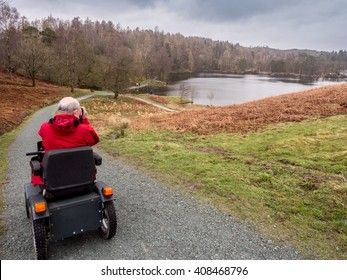 Tarn Hows, Coniston, UK. April 5th 2016. Photographer enjoying the great outdoors at Tarn Hows using a Tramper Mobility Scooter,