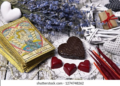 Tarot card Lovers, chocolate candies, heart and love symbols. The English title on the card