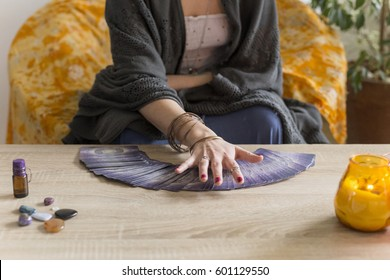 Tarot card reading session Woman`s  hand moving over the deck of tarot cards spread over the table