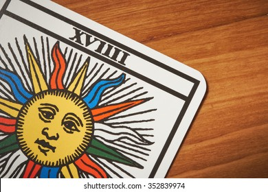 Tarot card sun for clairvoyance and divination on wooden table