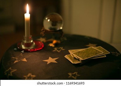 Tarot card table with tarot, candle and crystal ball, close-up