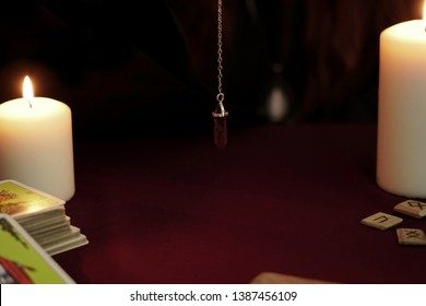 Tarot cards, amethyst magic stone pendulum on a chain, white candles and ancient wooden runes on dark mystic and vintage background. Occult, esoteric, divination and wicca concept.