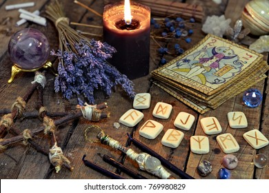 Tarot cards, ancient runes, black candle and pentagram. Occult, esoteric, divination and wicca concept. Mystic and vintage background