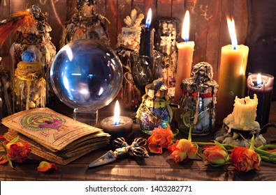 Tarot cards, burning candles, witch magic bottles and crystal ball. Wicca, esoteric, divination and occult background with vintage magic objects for mystic rituals