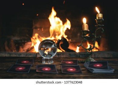 Tarot cards and crystal ball on fortune teller table on a burning fire background. Future reading concept. Divination.