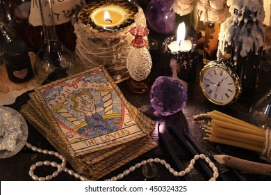 The tarot cards with crystal, black candles and magic objects. Halloween concept, ritual or spell with occult and esoteric symbols, divination rite. Love magic
