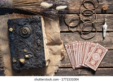 Tarot cards deck and book of magic on the old wooden table background.