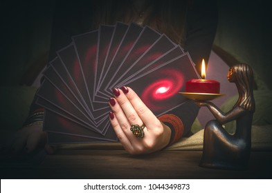Tarot cards deck in the hand of fortune teller. Future reading concept.