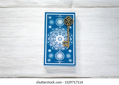 Tarot cards deck and magic key on a white wooden table background.