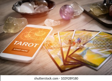 Tarot cards dowsing tool and smartphone with modern fortunetelling application on screen as a concept of psychic advisor or newest ways of divination