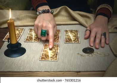 Tarot cards and fortune teller desk table. Future reading. Woman fortune teller shows with her index finger on tarot card.