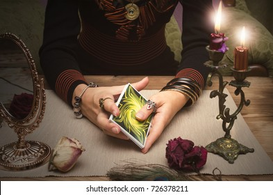 Tarot cards in fortune teller hands. Woman mixes tarot cards deck on wooden desk table. Reading future.