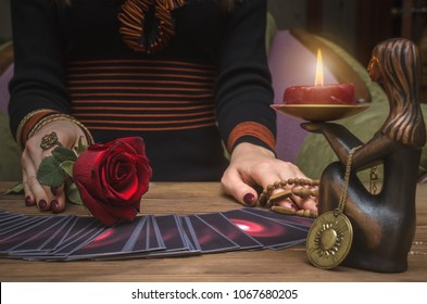Tarot cards and future reading concept. Fortune teller holding in hands a red rose flower and rosary beads. Romantic love divination.
