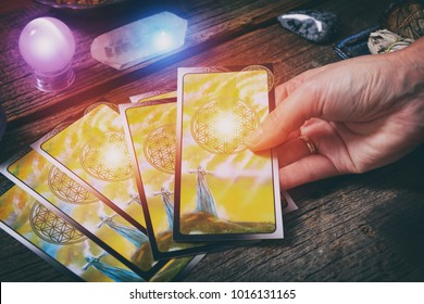 Tarot cards in hand, dowsing tool and crystals on a wooden board