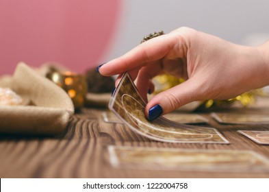 Tarot cards and hands of fortune teller on wooden table background.