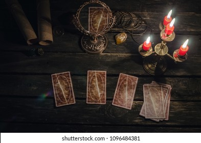 Tarot cards on fortune teller desk table background. Fortune reading concept. Magic mirror on paranormal table.