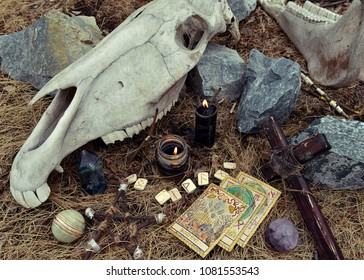 The tarot cards with ritual cross, runes, crystals and scary horse skull. Mystic background with ritual esoteric objects, occult and halloween concept