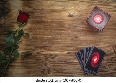 Tarot cards and rose flower on fortune teller desk table background. Future reading. Love or romantic divination concept.