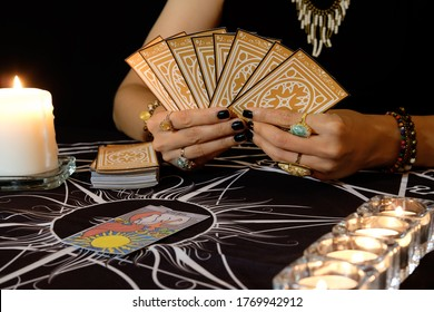 Tarot reader or fortune teller of hands holding up deck tarot cards.Tarot cards spread and The Sun card on table near burning candles.The Sun card portends good fortune, happiness ,joy and harmony.